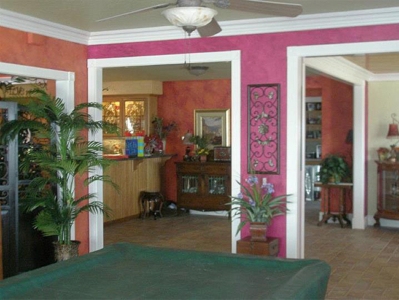 A menagerie of wonderful vibrant colors. Walls are faux finished in bright shades of pink, orange with deep red highlights, and greens.